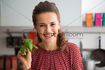 Portrait of happy young housewife showing fresh basil