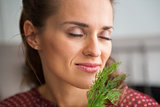 Portrait of young housewife enjoying fresh dill