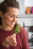 Portrait of young housewife holding fresh dill