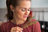 Portrait of young housewife enjoying fresh thymus