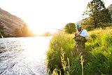 Fly fisherman on the river bank at sunrise