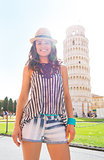 Portrait of happy young woman standing in front of leaning tower