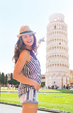 Happy young woman pointing on leaning tower of pisa, tuscany, it