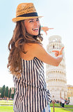 Happy young woman framing leaning tower of pisa, tuscany, italy