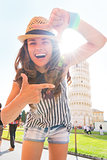 Happy young woman framing in front of leaning tower of pisa, tus