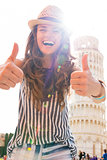 Happy young woman showing thumbs up in front of leaning tower of