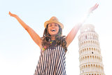 Happy young woman rejoicing in front of leaning tower of pisa, t
