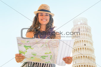Portrait of smiling young woman with map in front of leaning tow