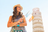 Happy young woman with italian flag in front of leaning tower of