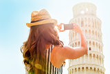 Young woman taking photo of leaning tower of pisa, tuscany, ital