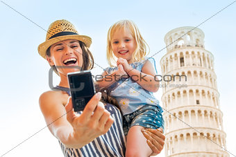 Portrait of happy mother and baby girl making selfie in front of