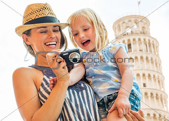 Portrait of happy mother and baby girl checking photos in camera