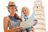 Happy mother and baby girl using map in front of leaning tower o
