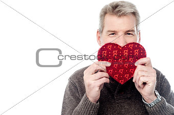 Mature man holding heart shaped gift box