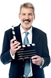 Smiling man showing a clapperboard to the camera