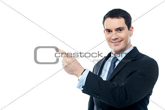 Smiling businesman pointing at something