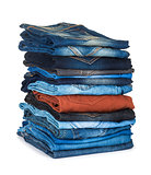 high stack of colored jeans on a white background