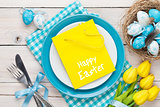 Easter with yellow tulips, colorful eggs and gift bag