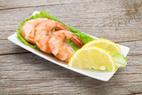Cooked shrimps with lemon and salad leaves