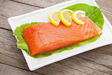 Fresh salmon fish with lemon and salad leaves
