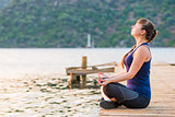 girl with a long braid relaxes in a lotus position on the pier