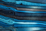 stack of different shades of blue jeans as a background