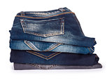 stack of blue jeans on a white background