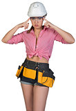 Woman in tool belt and hard hat adjusting protective glasses