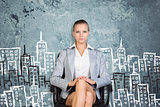 Businesswoman sitting against wall with sketch of city