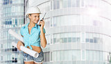 Woman in hard hat holding drawing rolls, talking on walkie talki