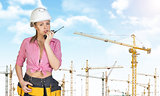 Woman in hard hat and tool belt talking on walkie talkie