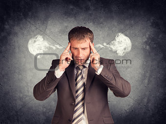 Stressed businessman thinking with his fingers on temples, smoke from ears
