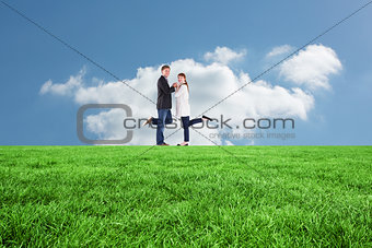 Composite image of smiling couple with raised legs