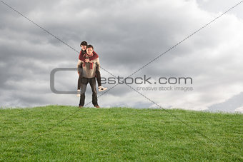 Composite image of man giving girlfriend piggy back