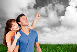 Composite image of happy couple looking upwards