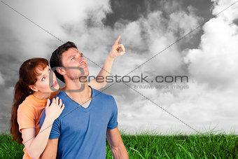 Composite image of happy couple looking upwards