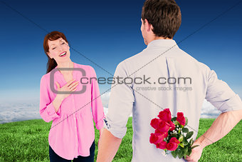 Composite image of man holding roses behind him
