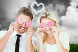 Composite image of attractive young couple holding pink hearts over eyes
