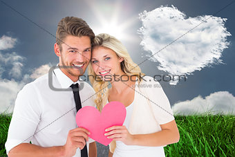 Composite image of attractive young couple holding pink heart