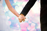 Composite image of mid section of newlywed couple holding hands in park