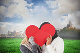 Composite image of couple in winter fashion posing with heart shape