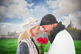 Composite image of smiling couple in winter fashion posing with roses