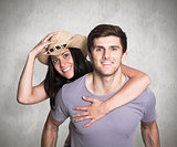 Composite image of man giving his pretty girlfriend a piggy back