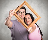 Composite image of young couple holding up frame