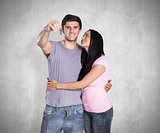 Composite image of young couple showing keys to house