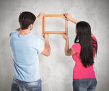 Composite image of young couple hanging a frame