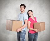 Composite image of young couple holding moving boxes