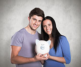 Composite image of young couple holding a piggy bank