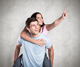 Composite image of young man giving girlfriend a piggyback ride