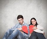 Composite image of young couple sitting on floor with broken heart